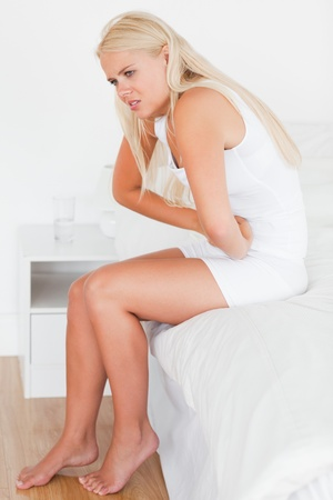 Portrait of a woman having a stomachache in her bedroom Stock Photo - 11232221