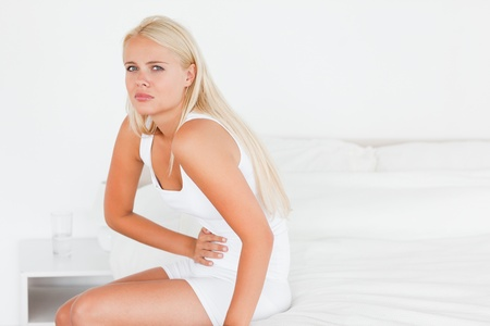 Sick woman having a stomachache in her bedroom Stock Photo - 11211765