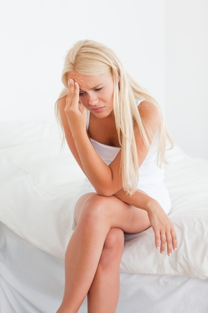 suffering: Portrait of an ill blonde woman in her bedroom Stock Photo