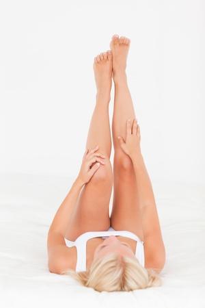 depilacion: Una mujer mirando a sus piernas sobre un fondo blanco Foto de archivo