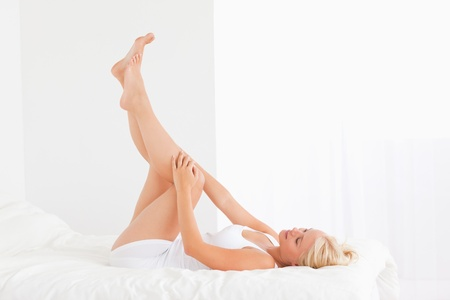 Fit woman with the legs up while lying on her bed photo