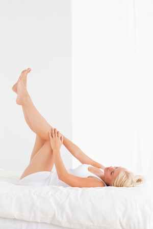 Portrait of a woman with the legs up in her bedroom photo