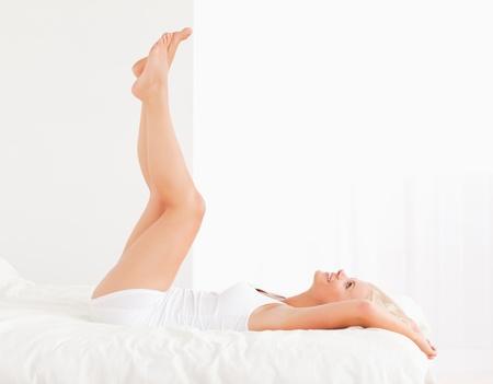 depilacion: Atractiva mujer con las piernas elevadas mientras se est� acostado en su cama