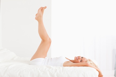 aesthetic: Smiling woman with the legs up while lying on her bed