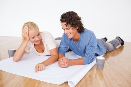 Couple looking at a plan while lying on the floor photo