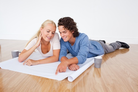 Young couple looking at a plan while lying on the floor photo