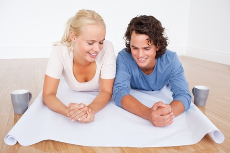 Close up of a couple looking at a plan with cups of coffee while lying on the floor photo