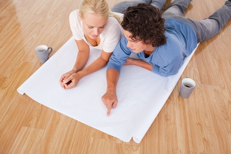 Man showing a point on a plan to his fiance while lying on the floor photo