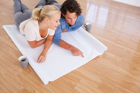 Cute man showing a point on a plan to his fiance while lying on the floor photo