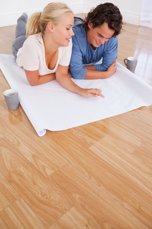 Portrait of a couple looking at their future room on a plan while lying on the floor photo