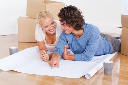 Happy couple getting ready to move in a new house while lying on the floor photo