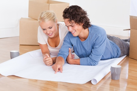 Young couple getting ready to move in a new house while lying on the floor photo