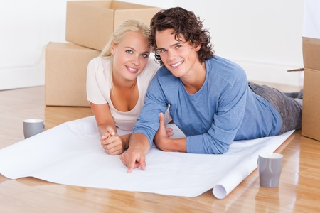 Couple getting ready to move in a new house looking at the camera photo