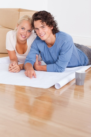 Portrait of a couple getting ready to move in a new house lying on the floor photo