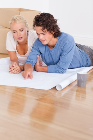 Portrait of a cute couple getting ready to move in a new house lying on the floor photo