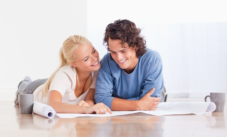 Cute couple getting ready to move in a new house while lying on the floor photo
