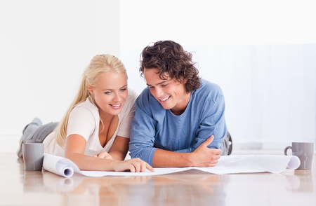 Smiling couple getting ready to move in a new house while lying on the floor photo