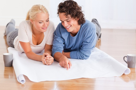 Couple organizing their new home while lying on the floor Stock Photo - 11226779