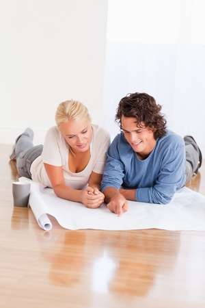 Portrait of a lovely couple organizing their new home while lying on the floor Stock Photo - 11191924
