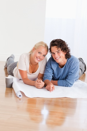 Portrait of a happy couple organizing their new home while lying on the floor Stock Photo - 11192090
