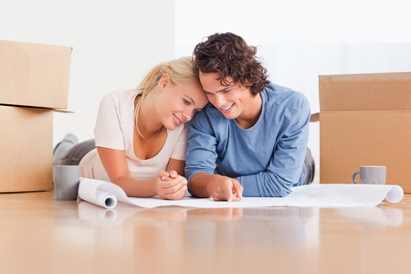 Happy couple organizing their new home surrounded by boxes photo