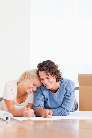 Portrait of an in love couple organizing their new home surrounded by boxes photo