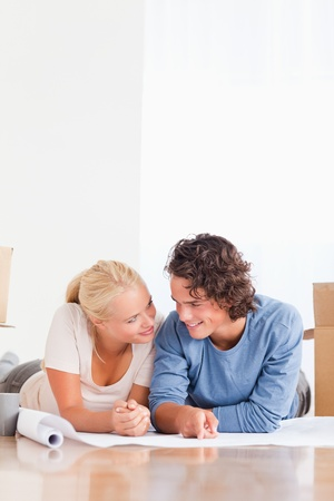 Portrait of an in love couple organizing their future home while lying on the floor photo