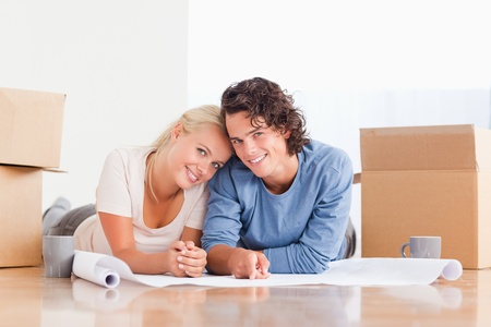 Couple organizing their future home surrounded by boxes photo