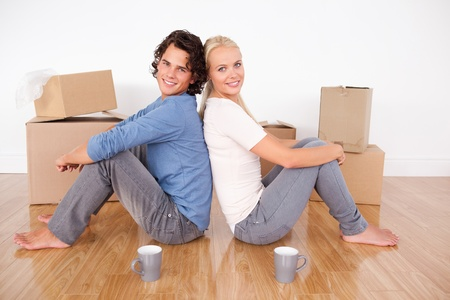 Couple sitting on the floor surrounded by boxes photo