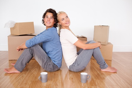 Lovely couple sitting on the floor surrounded by boxes photo