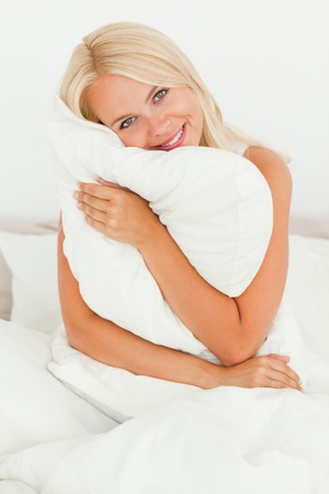 Woman holding a pillow sitting on her bed photo