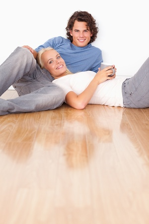 Portrait of a young couple sitting together on the floor photo
