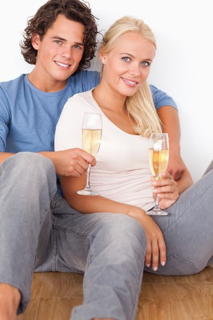 Portrait of a couple with glasses of sparkling wine sitting on the floor Stock Photo - 11227310