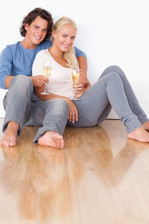 Portrait of a cute couple with glasses of sparkling wine sitting on the floor photo