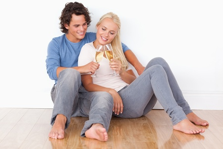 Portrait of a young couple toasting while sitting on the floor photo