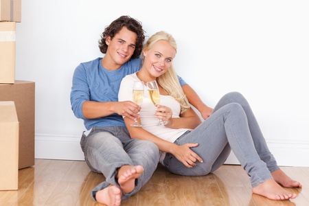 Young couple toasting while sitting on the floor photo