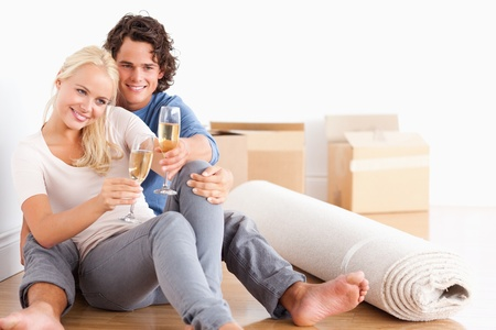 alcohol cardboard: Happy couple toasting while sitting on the floor Stock Photo