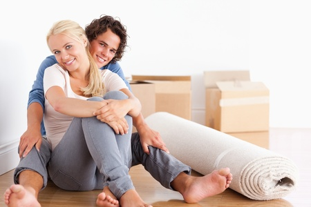 Happy couple sitting on the floor surrounded by boxes photo