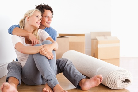 home moving: Smiling couple sitting on the floor looking away from the camera