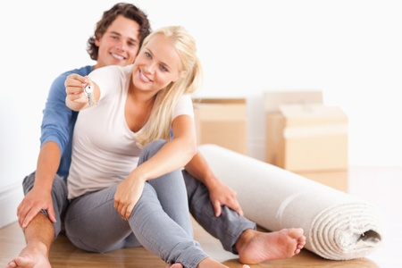 Woman sitting with her fiance giving keys with the camera focus on the keys photo