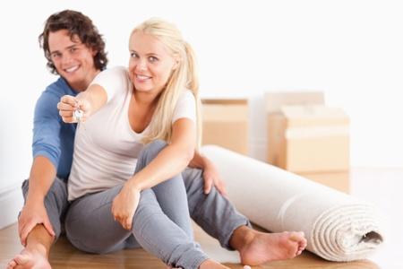 Woman sitting with her boyfriend giving keys looking at the camera photo
