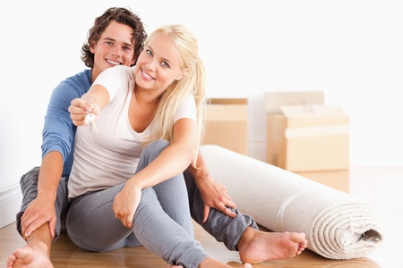 Cute woman sitting with her boyfriend giving keys while looking at the camera photo