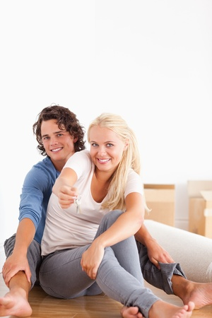 Portrait of a cute woman sitting with her boyfriend giving keys while looking at the camera photo