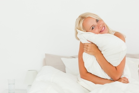Lovely woman holding a pillow while sitting on her bed photo