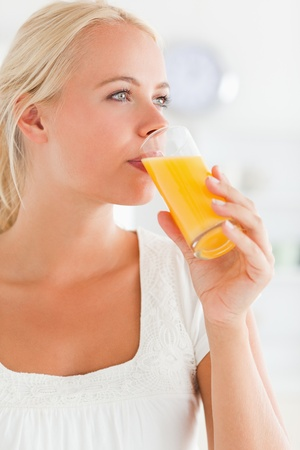 Portrait of a blonde woman drinking juice looking away from the camera photo