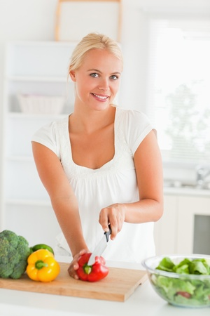Woman slicing pepper in her kitchen photo