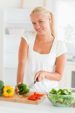 Lovely woman slicing pepper in her kitchen photo
