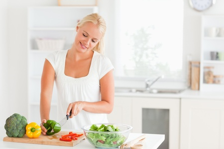 Beautiful woman slicing pepper in her kitchen photo
