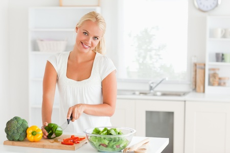 Good looking woman slicing pepper in her kitchen photo