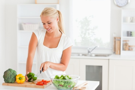 Blond-haired woman slicing pepper in her kitchen photo